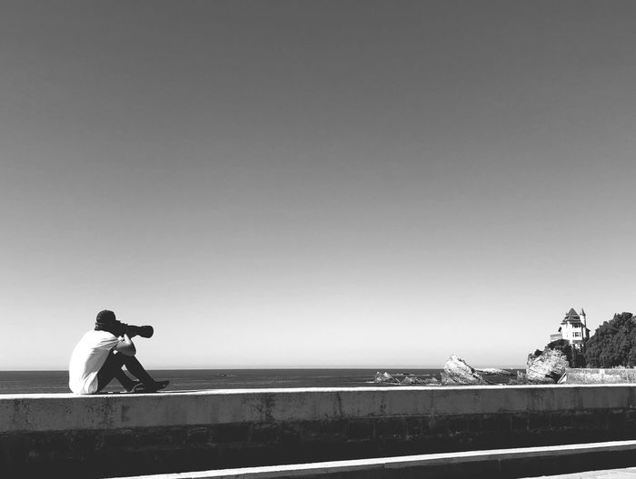 Rear view of man photographing while sitting on retaining wall against sea against clear sky