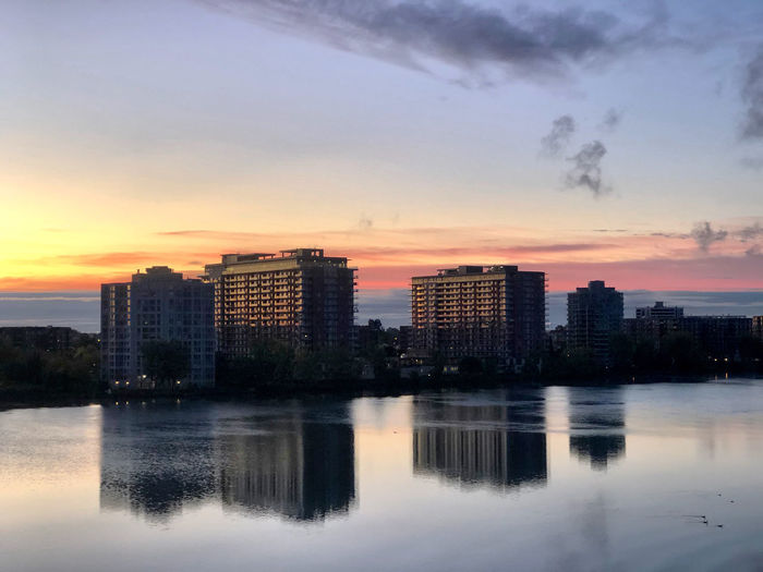 Scenic view of lake by buildings against sky during sunset