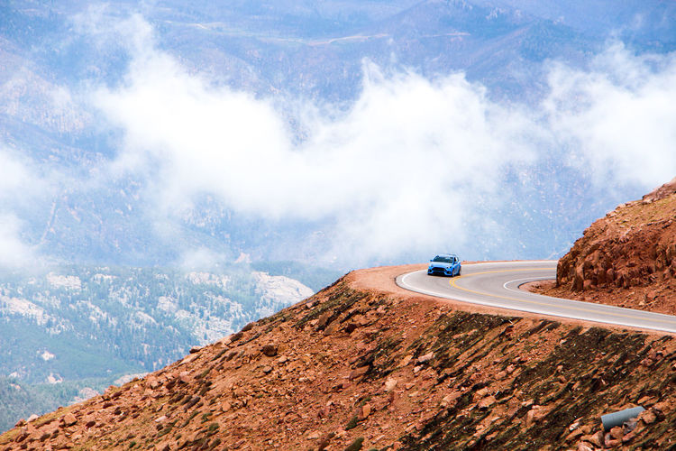 Car Moving On Road At Mountain Against Clouds