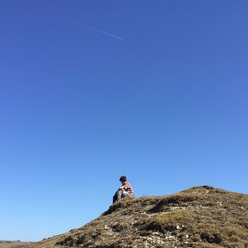 Low angle view of boy sitting on hill against clear sky