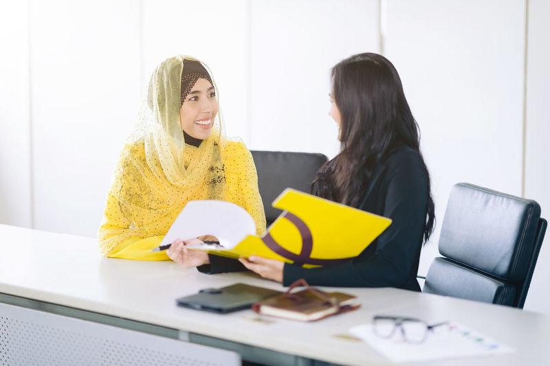 Smiling businesswomen sitting at desk in office