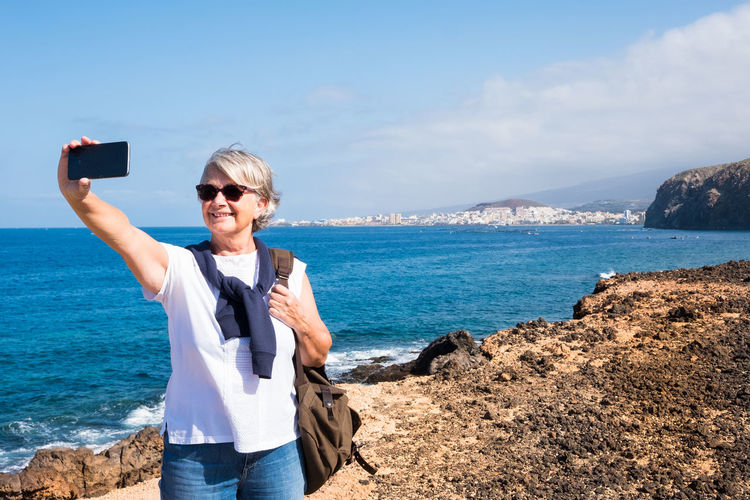 Woman taking selfie while standing on cliff by sea against sky