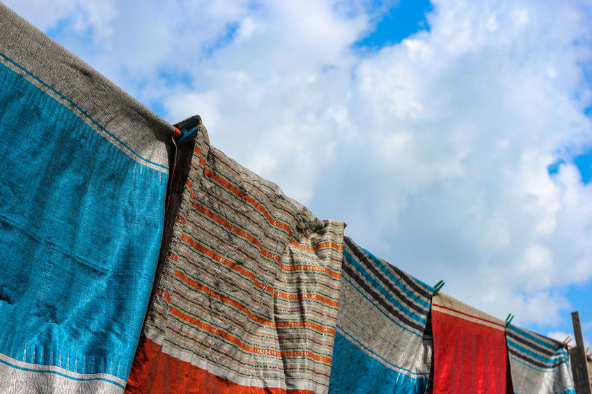 Thai traditional pattern cloth hanging above harvest rice farm Sky Cloud - Sky Textile Low Angle View Drying Multi Colored Day Hanging Nature Blue No People Clothing Laundry Clothesline Outdoors Towel Variation Material Choice Architecture Cloth Copy Space Pattern Hanging Clouds