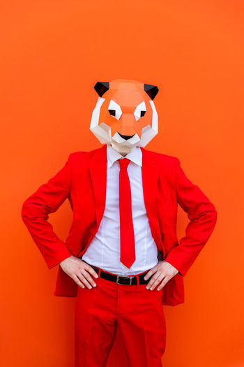 Person with toy standing against orange background