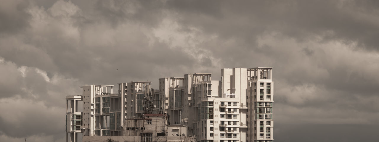 Low angle view of buildings against dramatic cloudy sky