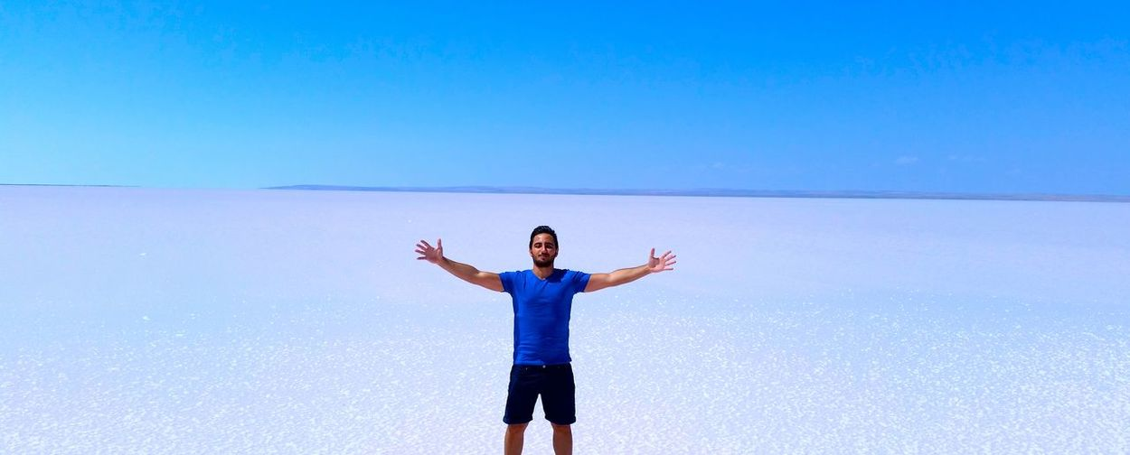Young man standing on salt flat against clear blue sky