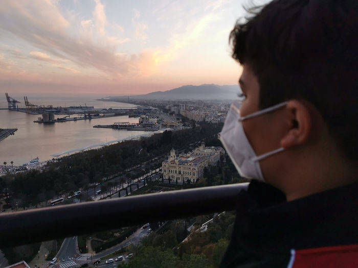 Portrait of man looking at cityscape against sky