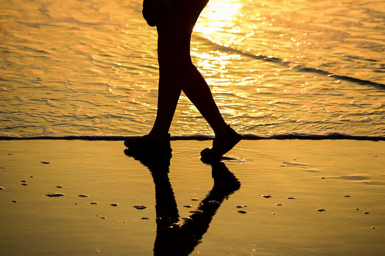 Low Section Of Silhouette Woman Walking On Sea Shore