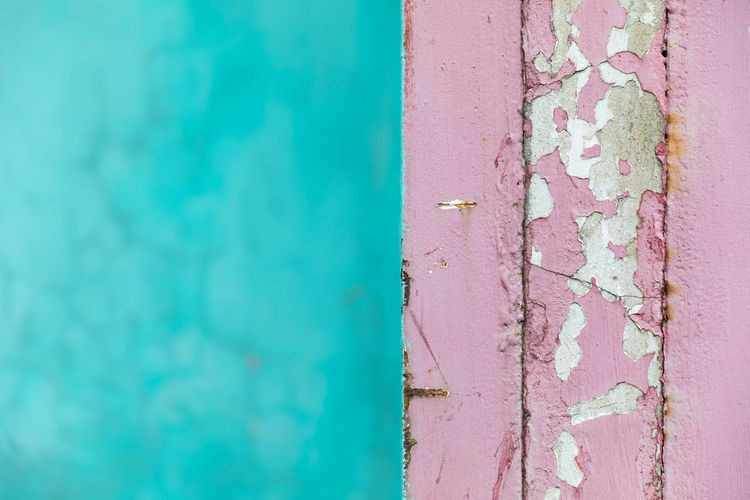 Pink paint coming off the corner of a wall against another turquoise colored cracked wall Abstract Aging Process Architecture Bad Condition Blue Building Exterior Built Structure Close-up Concrete Wall Copy Space Corner Cracked Damaged Deterioration Dividing Line Focus On Foreground Full Frame Paint Pastel Colored Peeling Off Pink Color Selective Focus Textured  Turquoise Colored Wall - Building Feature