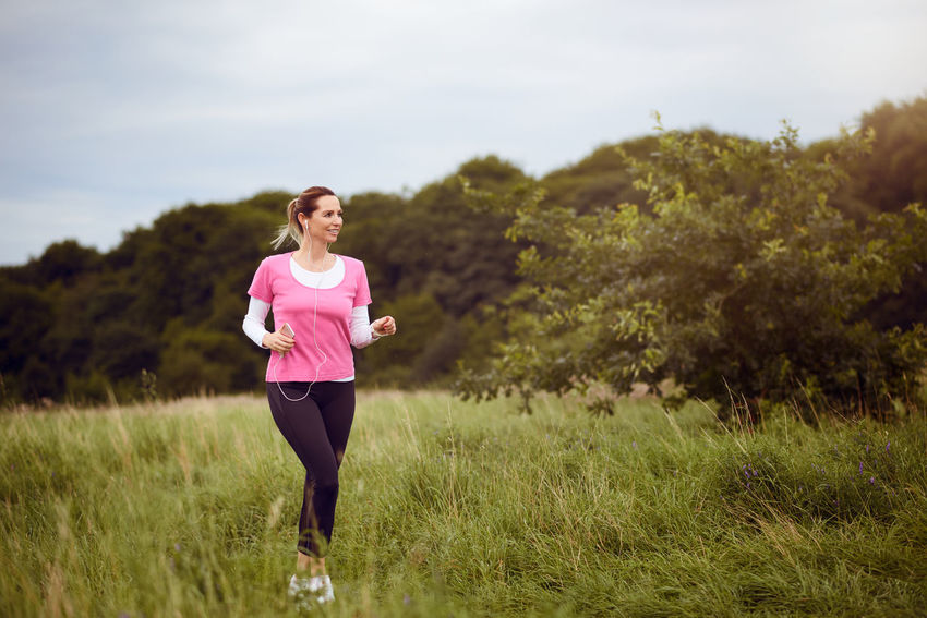 Fit middle-aged woman walking through a field Field Happiness Listening Music Nature Running Rural Trailrunning Woman Best Ager Countryside Cross-country Earbuds Exercising Fitness Healthy Lifestyle Jogging Lifestyles Middle-aged One Person Outdoors Smartphone Smiling Sports Sports Clothing