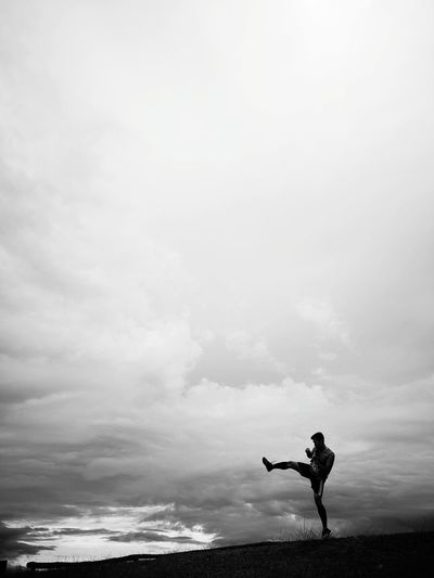 Silhouette Man Kicking On Landscape Against Sky