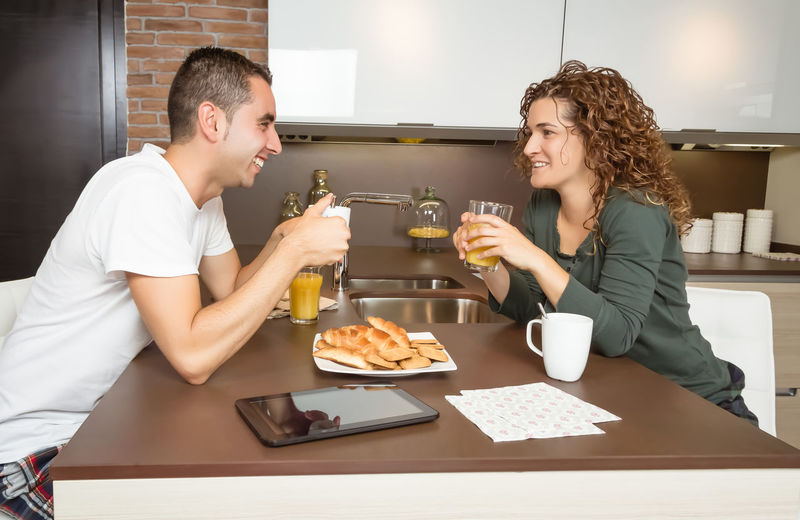Happy young love couple speaking and having a good breakfast in the home kitchen Young Woman Wife Two Together Thirties Technology Tablet Smiling Smile Relaxing Relationship People Orange Newspaper News Morning Meal Man Male Love Lifestyle Kitchen Juice Interior Indoors  Husband Home Healthy Happy Happiness Glass Girlfriend Girl Fruit Food Female Family Drink Digital Cup Couple Coffee Cheerful Caucasian Breakfast Boyfriend Adult 30s
