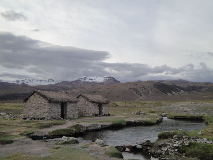 Houses By Stream Against Cloudy Sky
