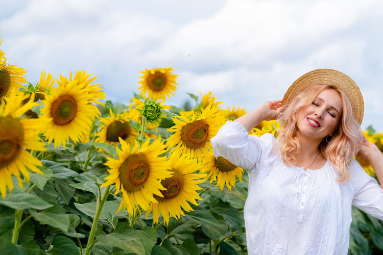 Portrait of smiling woman standing against sunflower