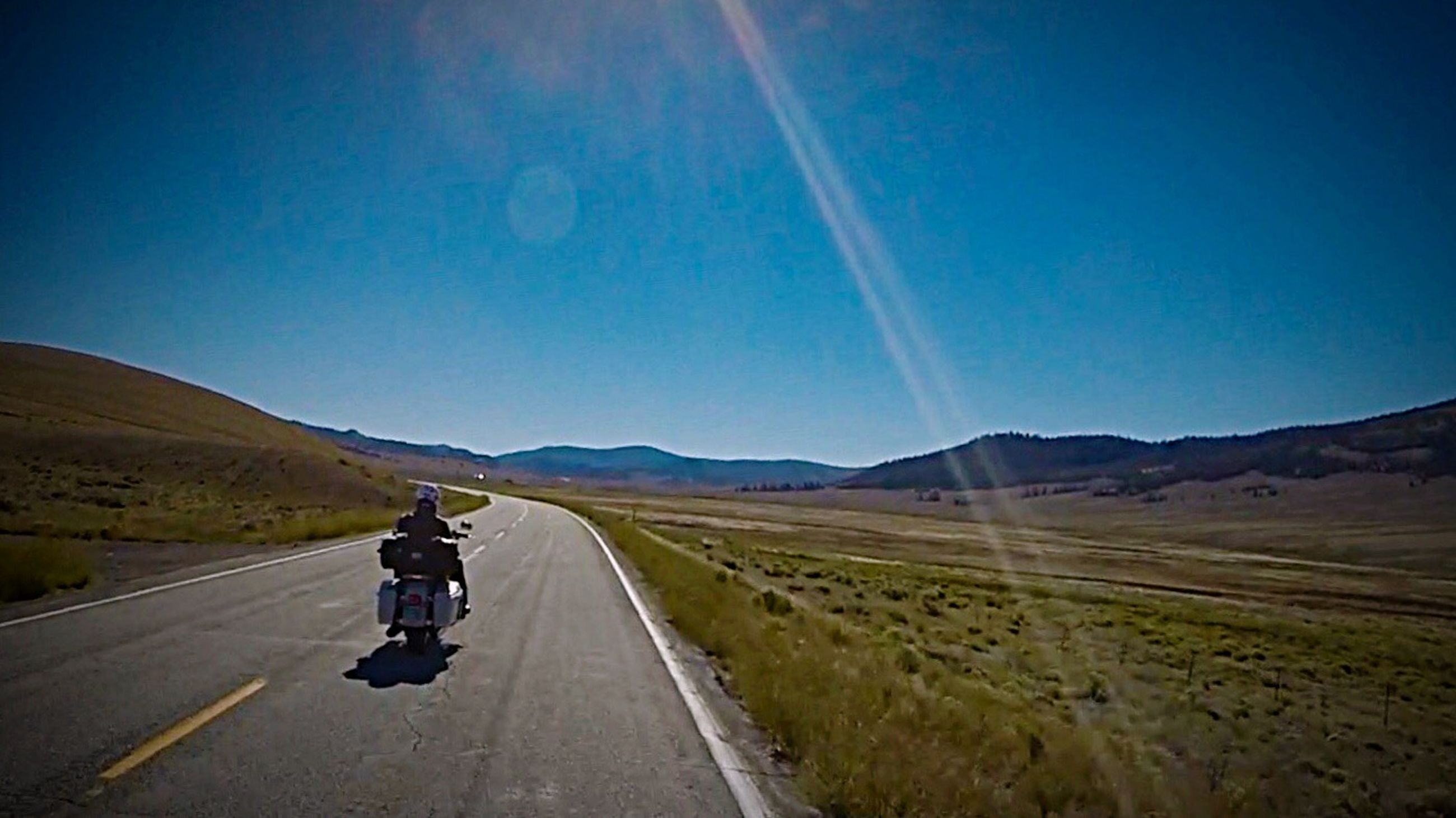 road, landscape, blue, the way forward, motorcycle, individuality, transportation, one man only, outdoors, desert, one person, rear view, scenics, sky, people, beauty in nature, only men, winding road, nature, adults only, adult, day, motorcycle racing