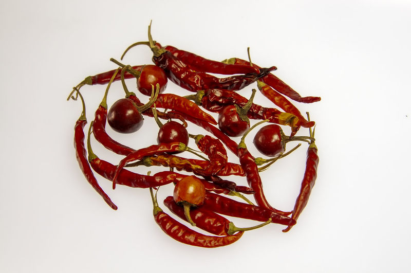 High angle view of red chili pepper against white background