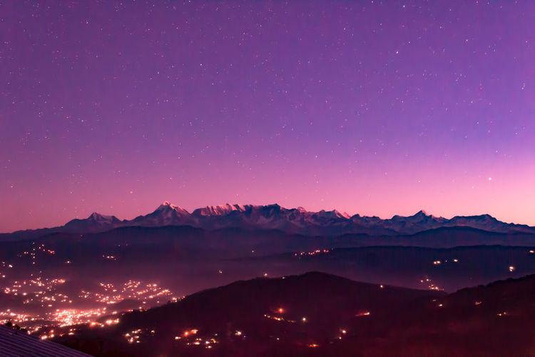 Silhouette mountains against sky at night