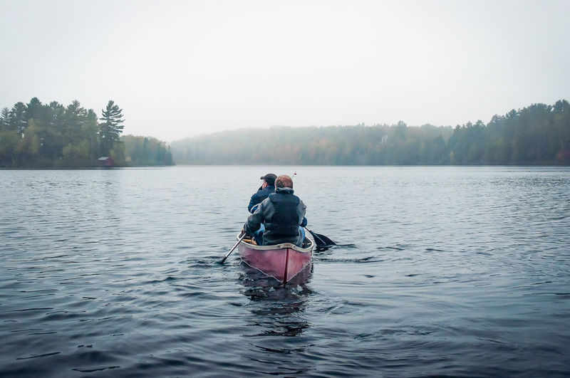 Rear view of man on boat in lake against sky