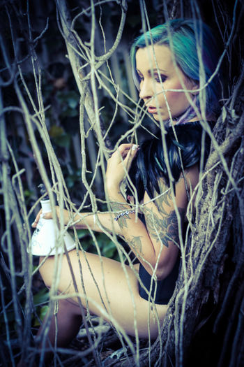 Sensuous model in fetish wear sitting tree