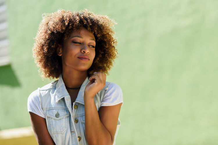 Close-Up Of Young Woman With Curly Hair Against Green Wall