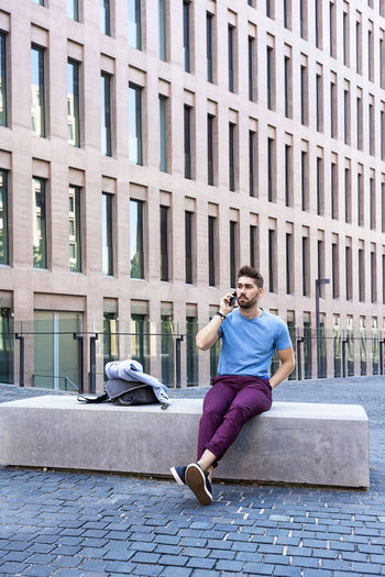 Portrait of young man sitting on building in city