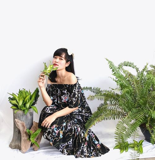 Young woman looking away while sitting on plant
