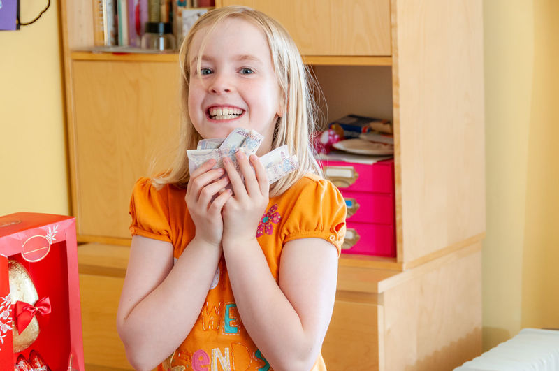 Portrait of smiling girl holding indoors at home