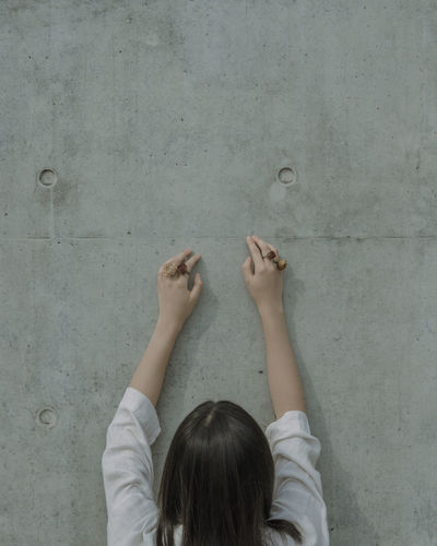 Rear view of young woman wearing rose shape rings by wall