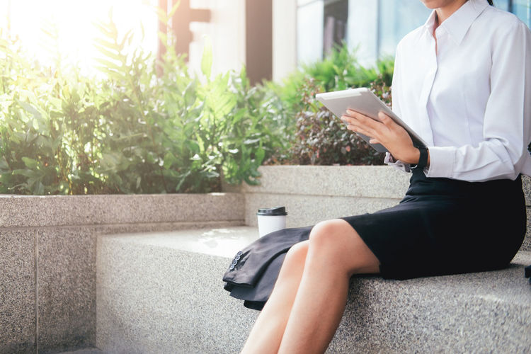 Midsection of businesswoman using digital tablet while having coffee at park