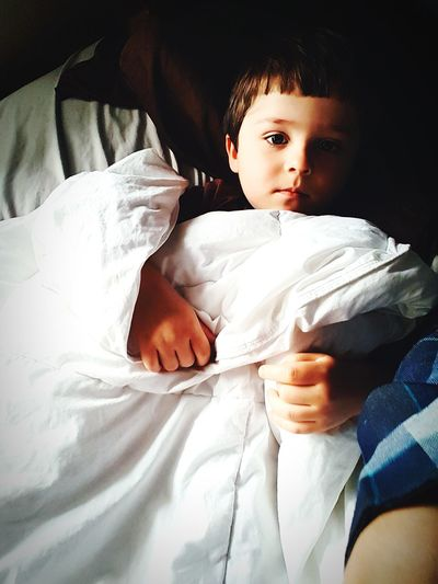Portrait Of Cute Boy Lying On Bed At Home