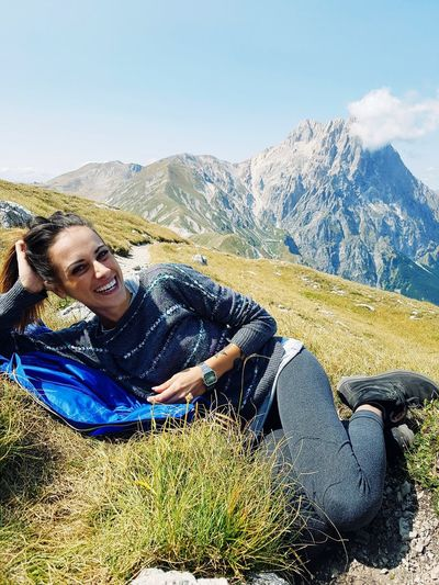 Portrait of smiling young woman sitting on mountain against sky