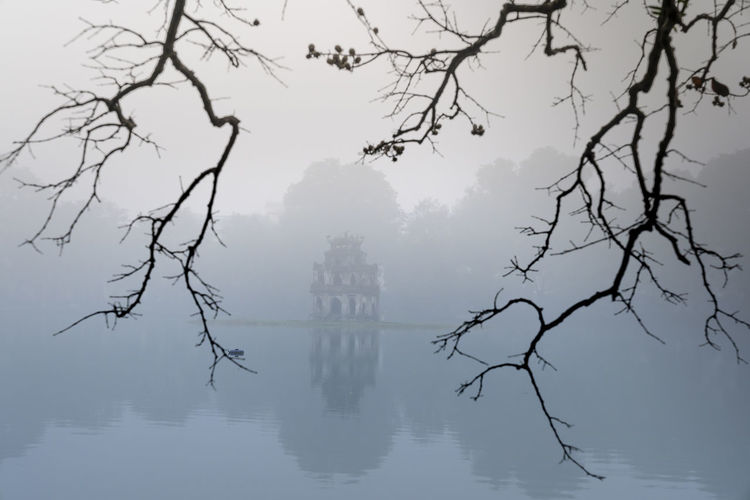 Hoan Kiem Lake ( Ho Guom) in the center of Hanoi in the fog in the morning. Hoan Kiem Lake is a famous tourist place in Hanoi Tourism ASIA Tower Dry Capital Cultural Magical Season  Landscape Tree Outdoors Winter Park Bright Flowers Plant Travel Sword Vietnam Leaf Symbol Old Lake Hanoi Vietnam  Famous Place Fog Foggy Background Ancient Blue Hoan Kiem Lake