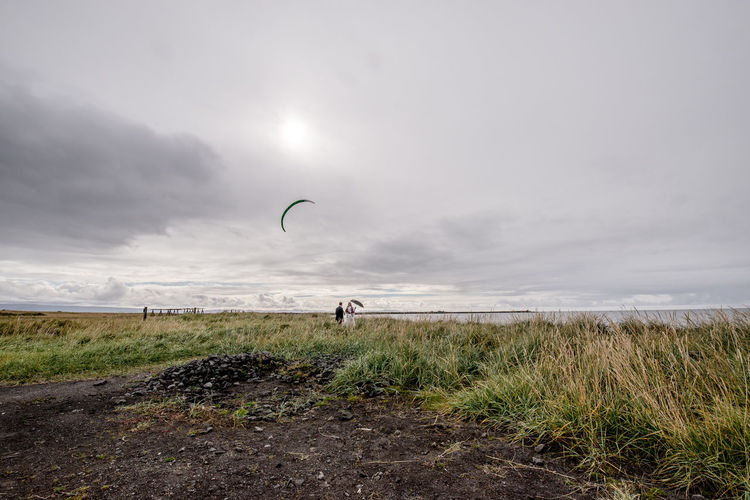 Man on field by sea against sky