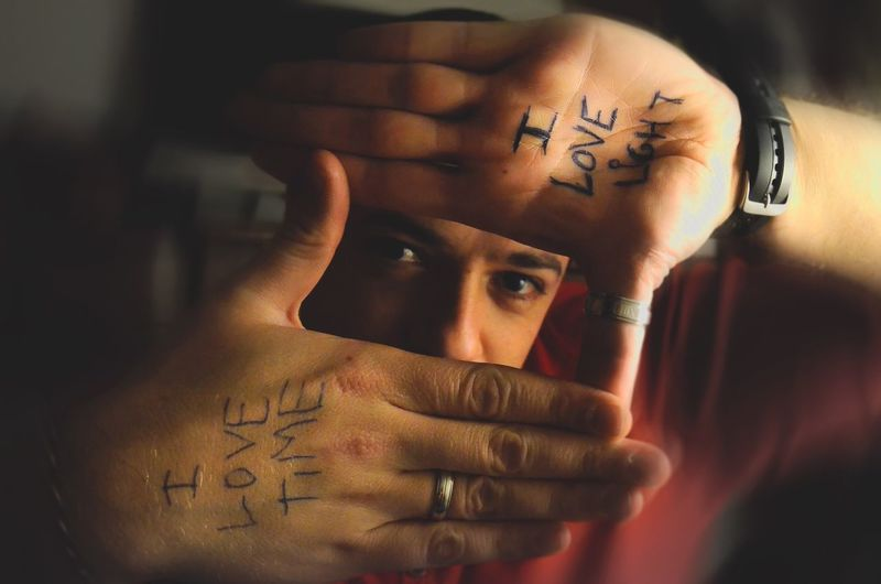 One Person Portrait Headshot Looking At Camera Young Adult Human Hand Visual Creativity Real People Body Part Human Body Part Young Men Indoors  Front View Hand Focus On Foreground Human Face Text