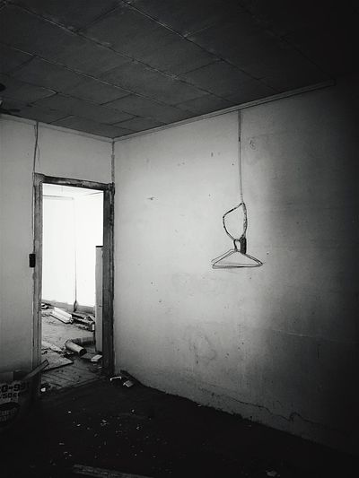 """""""Last Hanging"""" Three hangers are left in an empty room mysteriously dangling from a heavy electric cable in an abandoned old house in the Village of Corona, New Mexico, USA. Hangers Abandoned Abandoned & Derelict Old House Blackandwhite Photography Newmexicophotography"""