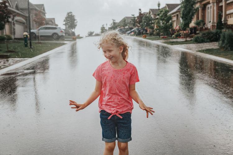 Happy girl standing on wet road during rainy season