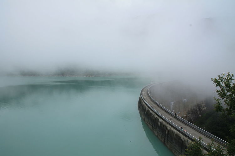 High angle view of dam by river against sky during foggy weather