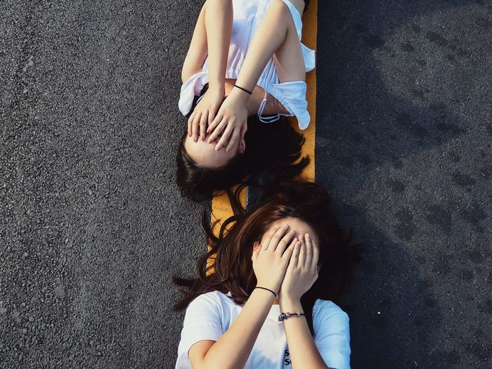 Directly Above Shot Of Women Covering Face While Lying On Road