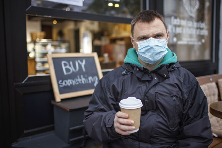 Portrait of man wearing mask holding coffee cup standing outdoors