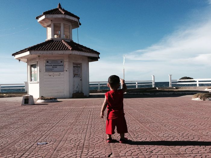 Rear view of boy standing by sea against sky