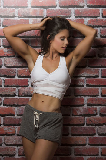 Beautiful Young Woman Standing Against Brick Wall