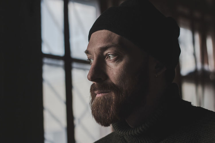 Beard Facial Hair Headshot One Person Real People Looking Portrait Men Mid Adult Men Looking Away Males  Focus On Foreground Close-up Lifestyles Hat Adult Mid Adult Indoors  Contemplation Mustache Human Face