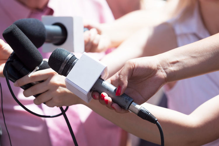 Midsection Of Reporters Holding Microphones