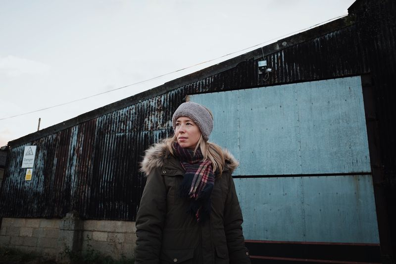 Woman wearing warm clothing looking away against building during winter
