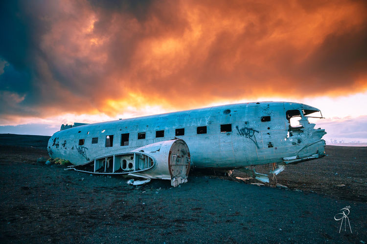 Abandoned airplane on runway against sky during sunset