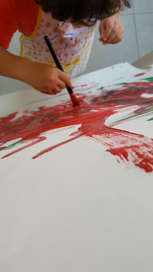 Close-up of hand holding paper painting on table