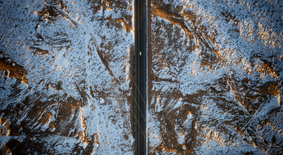Aerial View Of Road Amidst Snow Covered Land During Winter