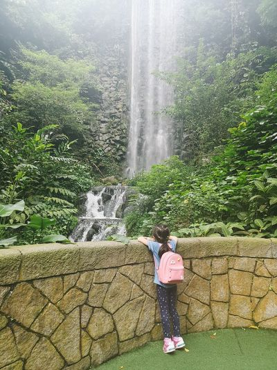 Full length of woman standing by waterfall