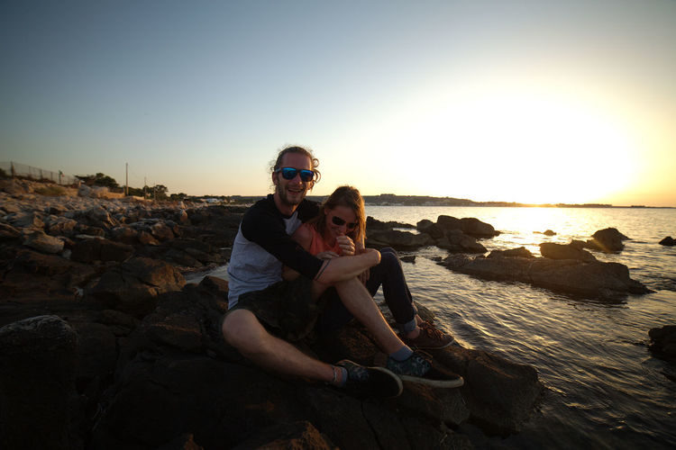 Happy Man And Woman Sitting On Rocks At Beach Against Sky During Sunset