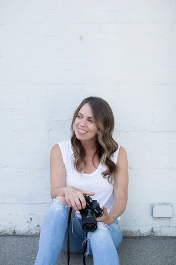 Portrait of a smiling young woman sitting against wall